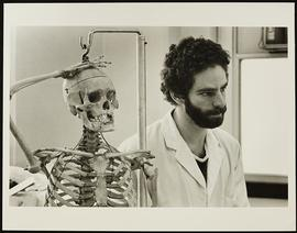 Unidentified man standing next to an anatomical skeleton model, Department of Anatomy, Washington...