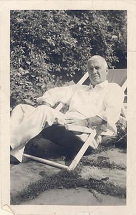 Portrait of E.V. Cowdry reclining in a lawn chair.