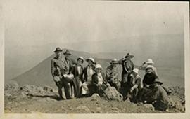Group portrait of Paul and June Stevenson with a group of young Western hikers on a barren hillto...