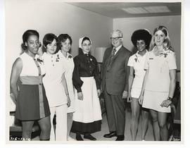 "Group portrait of C. Alvin Tolin and six female staff members wearing costumes for a ""nurses..."