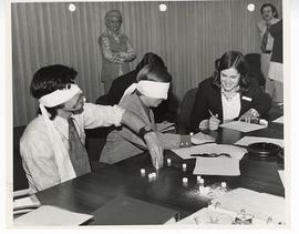Two blindfolded men stacking sugar cubes on a table as a woman and others look on, St. Louis Chil...