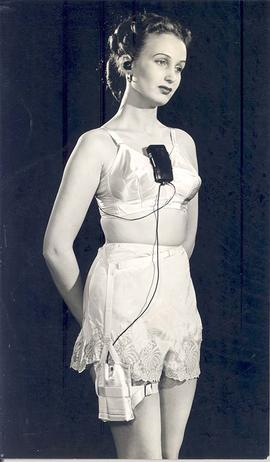 Woman modeling hearing device and battery harness attached to undergarments, circa 1950.