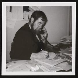 Portrait of Glyn Evans working at his desk in the Library.