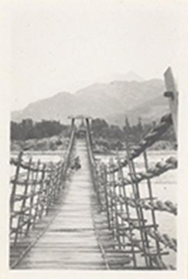 View across a wood and rope bridge with a distant figure carrying bundles, China.