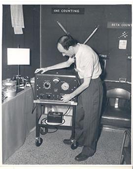 Man turning a knob of an Autoscaler machine at the Fourth International Cancer Research Congress,...