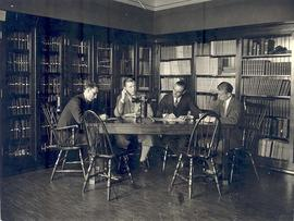 Four men seated at a table in the CID library demonstrating the Desk-top hearing instrument, circ...