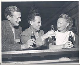 Two men and a woman toasting with glass bottles of Coca-Cola, Fourth International Cancer Researc...