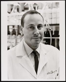 Portrait of Ralph D. Feigin in a laboratory coat.