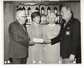 Unidentified man wearing a Stag Beer jacket and two unidentified women presenting C. Alvin Tolin ...