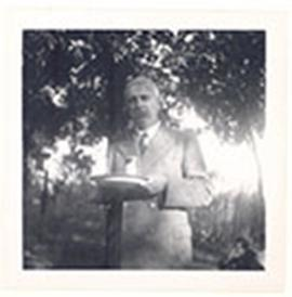 Portrait of E.V. Cowdry holding a plate at the Suntzeff's garden party.
