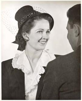 Woman wearing decorative earring, for Sonotone advertisement, circa 1950.