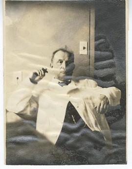 Henry Schwarz seated, smoking a cigar.