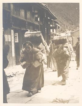 Two women walking down a street with large bundles strapped to their backs, Tibetan borderlands.