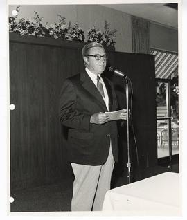 Unidentified man standing at a microphone.
