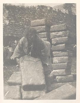 Man stacking large bundles, Tibetan borderlands.