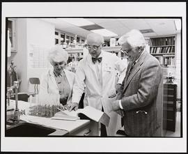 William Daughaday with an unidentified man and woman in a laboratory.