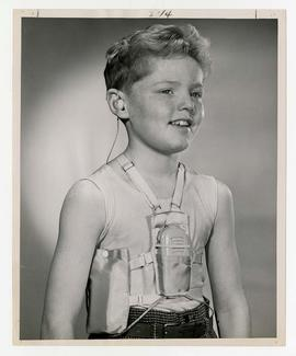 Young boy modeling hearing device and battery harness attached to undergarments, for Sonotone adv...
