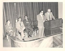 E.V. Cowdry and an unidentified man speaking at a podium onstage, with three other men seated beh...