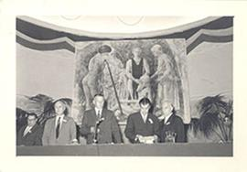 E.V. Cowdry standing on a speakers' dias with four unidentified men.