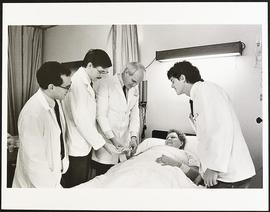 Dr. Samuel Wells examining a patient with third year students Tom Reinsel and Steven Shields and ...