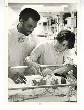 Man and nurse attending to an infant in the Neonatal Intensive Care Unit, St. Louis Children's Ho...