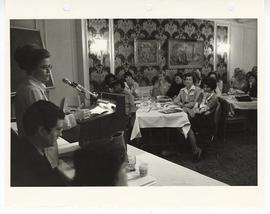 Unidentified woman addressing a primarily female audience sitting at tables.