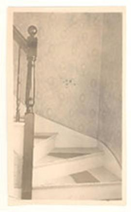 Interior view of a staircase and banister with a newel post.