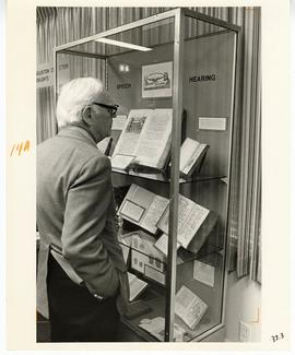 Donald A. Tatman examining a exhibit case containing highlights from the Max A. Goldstein rare bo...