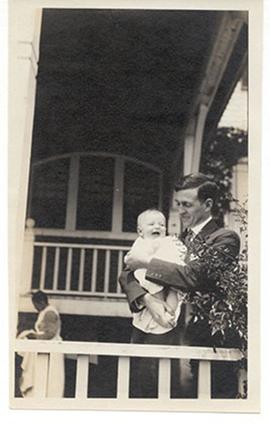 E.V. Cowdry holding Edmund Vincent Cowdry, Jr. on a porch.