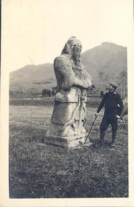 Paul H. Stevenson examining a carved stone warrior, Ming tombs, Beijing.