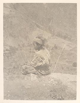 Young boy or girl sitting on a rocky hillside, Tibetan borderlands.