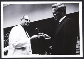 Harry Huth handing a glass swan to Bob Chase of KSD-TV.
