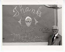 "C. Alvin Tolin posing next to a ""Thank You"" sign at an appreciation party."