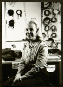 Portrait of an unidentified woman seated in front of a wall hung with audio equipment.