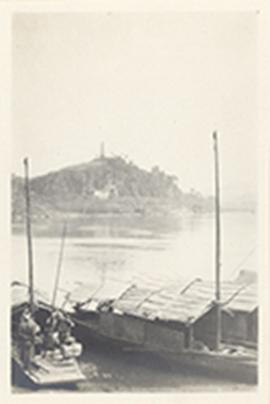Boats at a dock taking on passengers with a view of a settlement on the opposite shore, China.