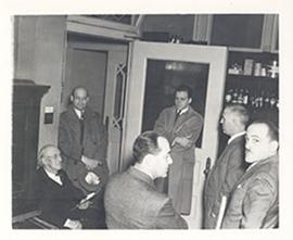 E.V. Cowdry and five other men gathered in a room with shelves of pharmaceutical jars.