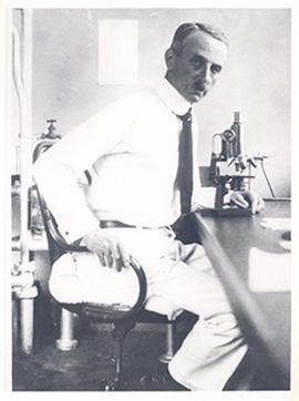Portrait of Leo Loeb seated in front of a microscope in a laboratory.