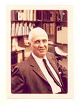 Portrait of E.V. Cowdry sitting at a desk with bookshelves behind him.
