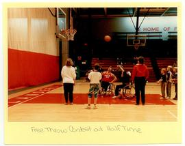 View of a free throw contest at halftime of a benefit wheelchair basketball game.