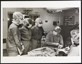 Dr. Charles Anderson performing surgery as three students observe, Department of Surgery, Washing...