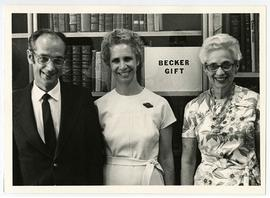 Group portrait of Bernard Becker, Janet Becker, and Estelle Brodman posed in front of the Becker ...