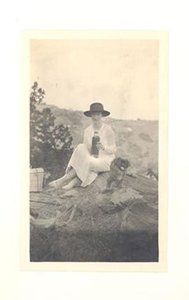 Portrait of Alice Cowdry picnicking in China with a hamper, thermos, and small dog.