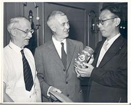 E.V. Cowdry, accepting an envelope and a decorated canister, and two unidentified men.