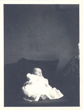 Portrait of an infant, likely Alice Moira Cowdry, on a bed.