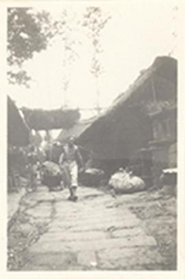 Man walking along a stone-paved road carrying balanced bundles on a pole across his shoulders, Ch...