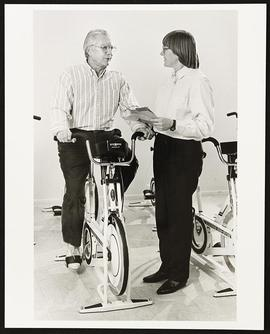 Portrait of Wendy Kohrt interviewing a patient on an exercise bicycle.