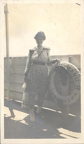Portrait of June Stevenson standing on the deck of the Siberia Maru next to a hanging lifesaver.