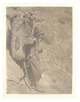 Man with a large basket strapped to his back leaning against a rock to rest, China.