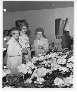 Three women examining flower arrangements, possibly at a St. Louis Children's Hospital Auxiliary ...