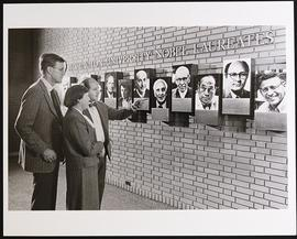 Paul Anderson, Mabel Purkerson, and Gerald Fischbach examining the Nobel wall.